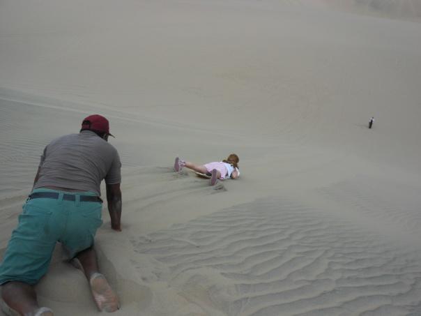 Sandboarding down dunes in Peru