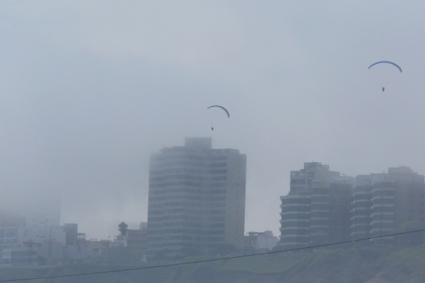 Paragliders over Miraflores and fog