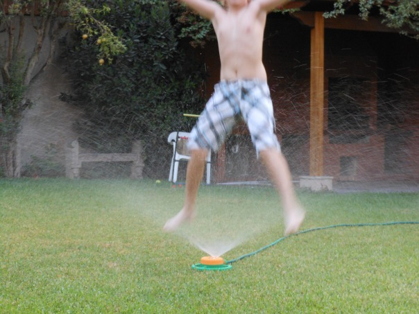 Child playing in sprinkler