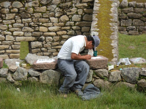 Worker painting signs at Machu Picchu