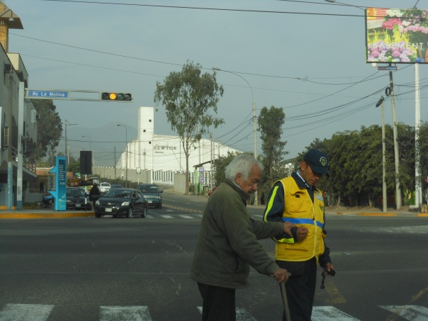 Person helps person cross street in Peru